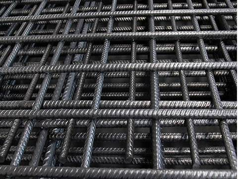 Many sheets of black concrete reinforcing square mesh.