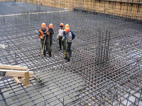 На строительной площадке на железобетонных армирующих сетках стоят пять квалифицированных рабочих.